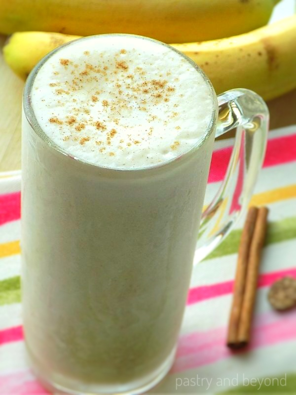 Banana Smoothie with ground cinnamon on top, bananas in the background
