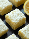 Lemon coconut bars on a black surface and a half lemon in the background.