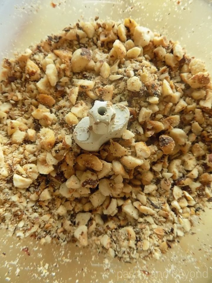 Hazelnuts chopped into big and small pieces in a food processor.