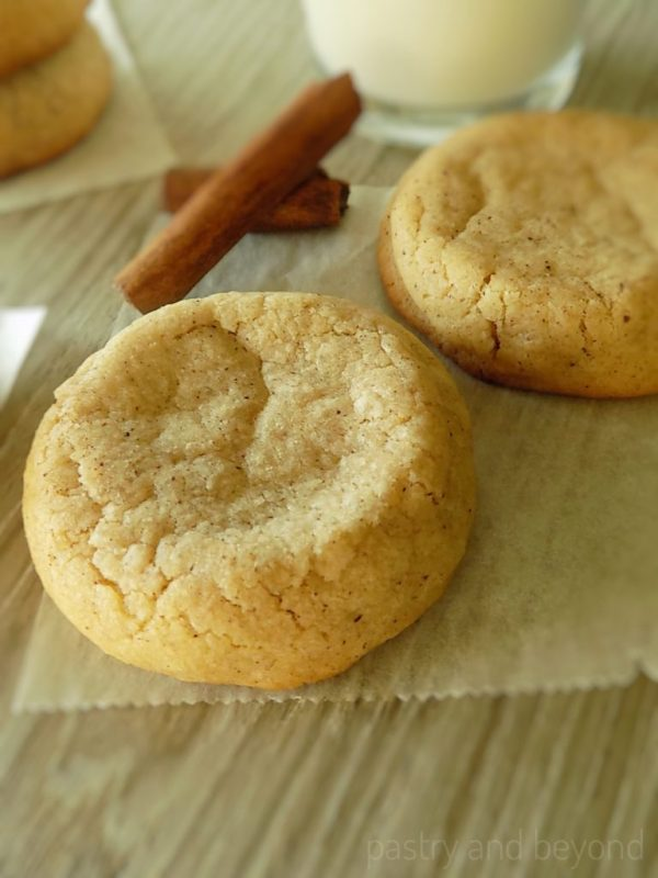 Soft cinnamon cookies with cinnamon sticks on a parchment paper.