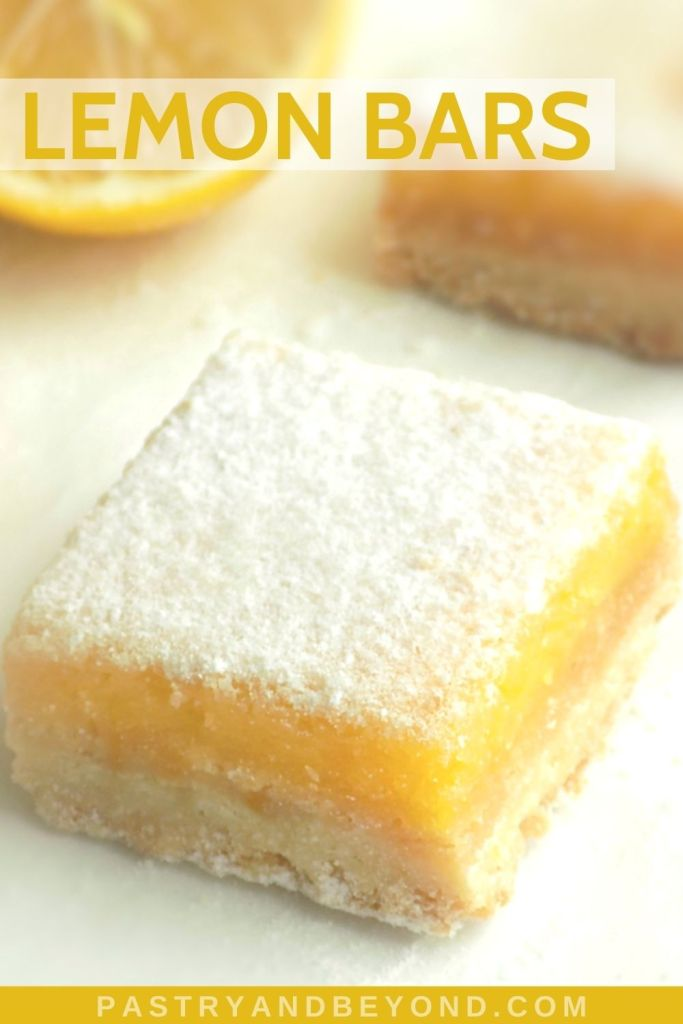 Lemon bars on a white surface with half lemon in the background.