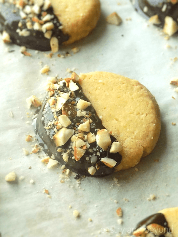 Almond Shortbread Cookies with crushed almonds on top on a parchment paper.