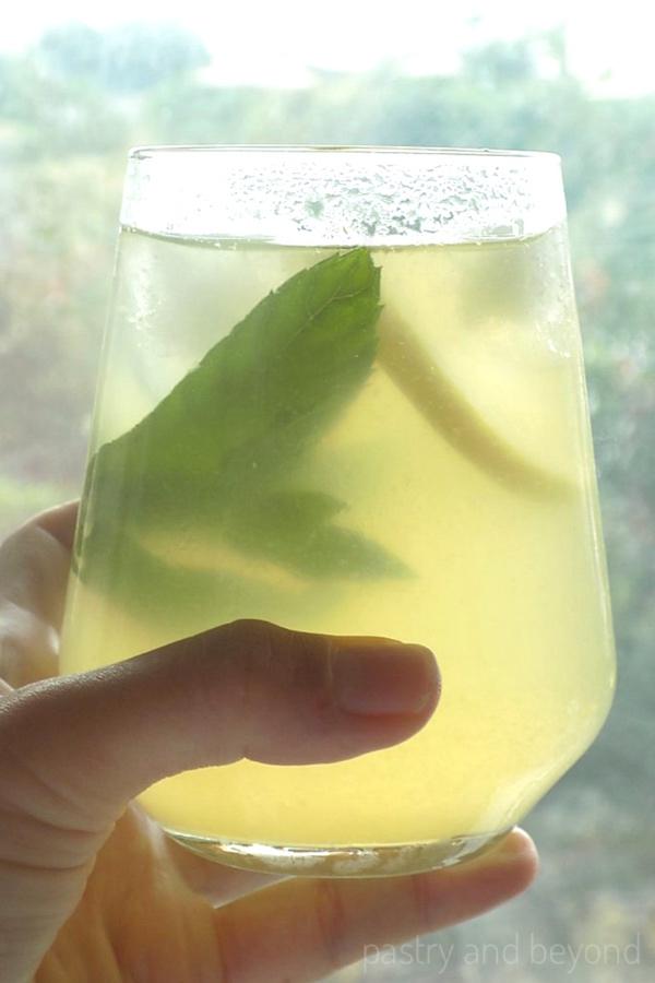 Holding a lemonade glass.