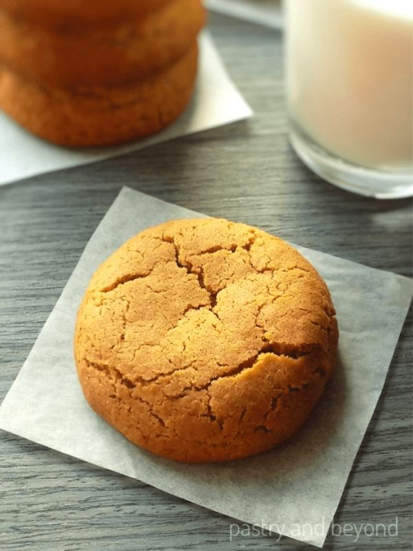 Soft Ginger Molasses Cookie on a blue-gray surface with milk and stacked cookies.