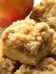 Apple pie bars with crumble topping with apple in the background.