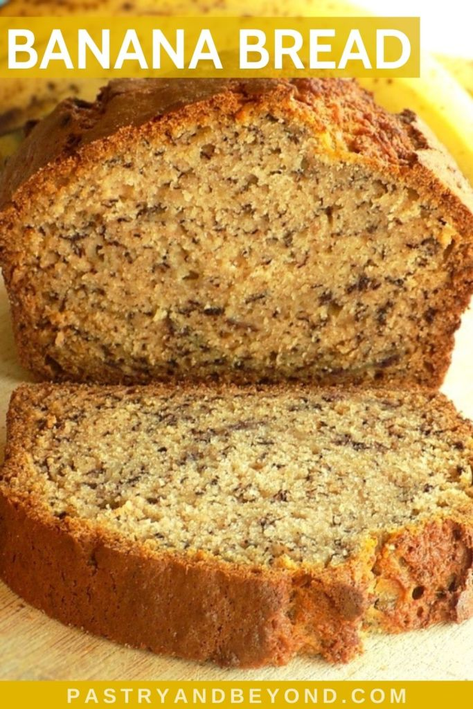 Banana bread with a slice on a wooden board with bananas in the background.