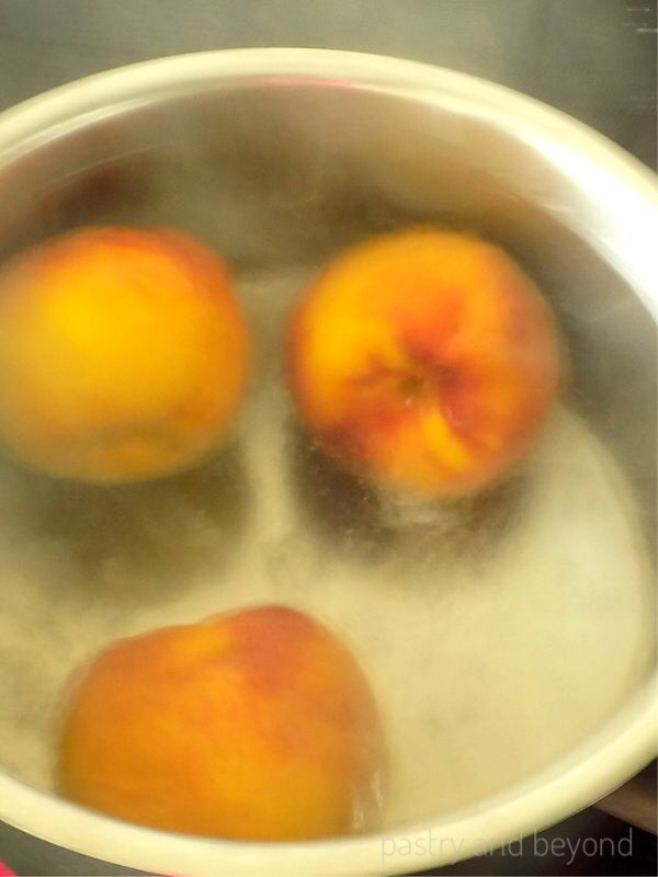 Three peaches are boiling in a pot.
