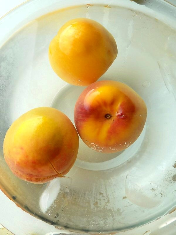 Three peaches in ice cold water to avoid cooking the peaches.