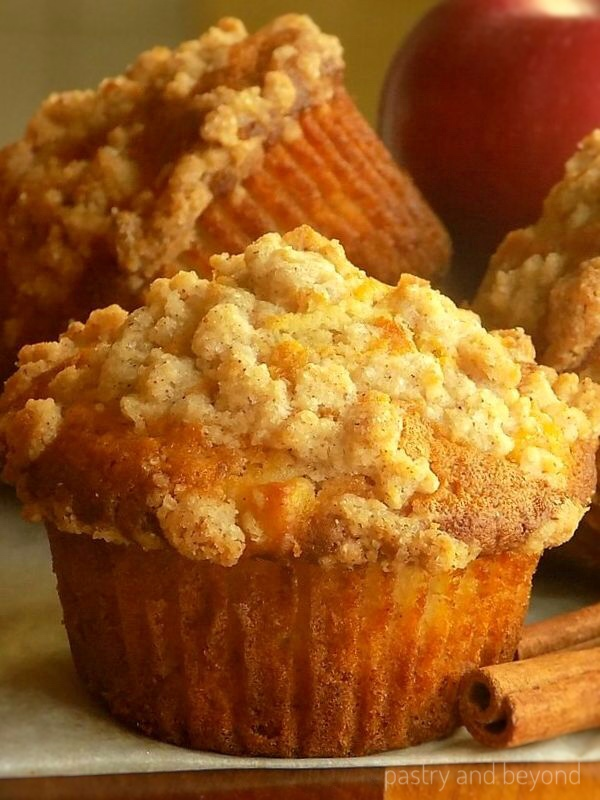 Apple Crumble Muffins with cinnamon sticks and apple on the background