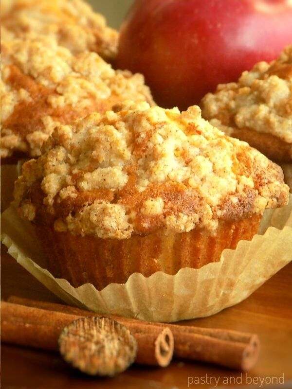 Apple Crumble Muffins on a wooden surface with the cinnamon sticks