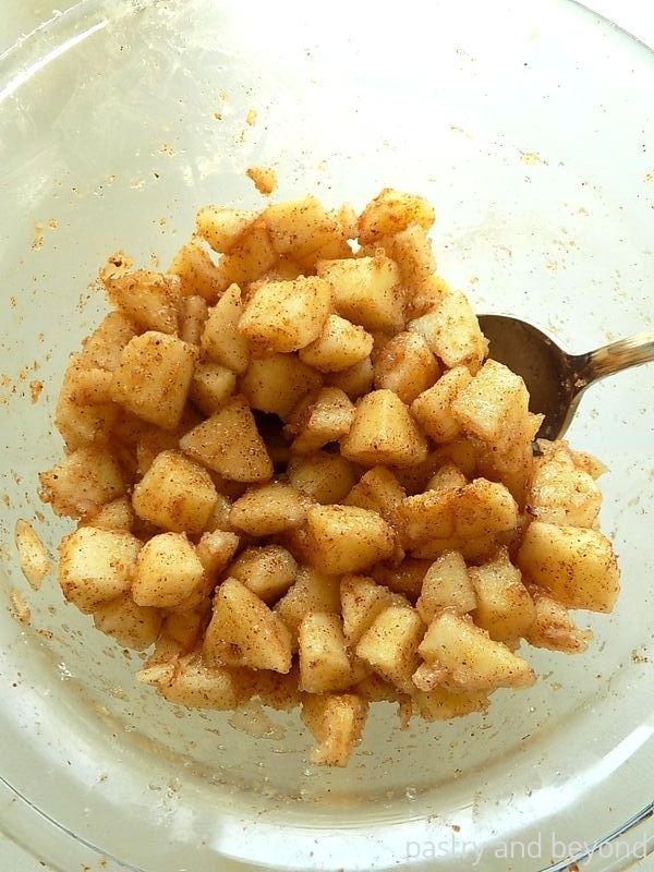 Cubed apples in a bowl mixed with sugar, cinnamon, nutmeg and cornstarch using a spoon.