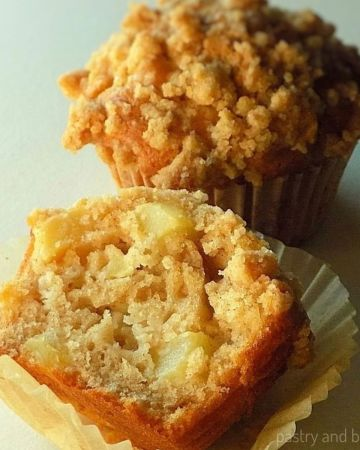 Half of the apple crumble muffin that is placed in front of the whole muffin.