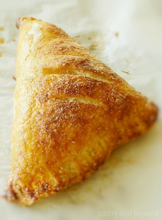 Large puff pastry apple turnover on a baking sheet.