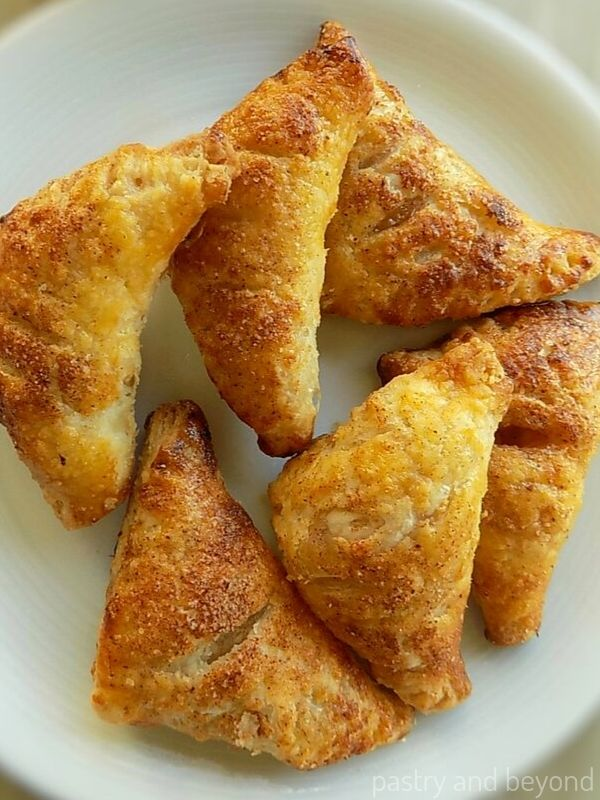 Six small apple turnovers on a white plate.