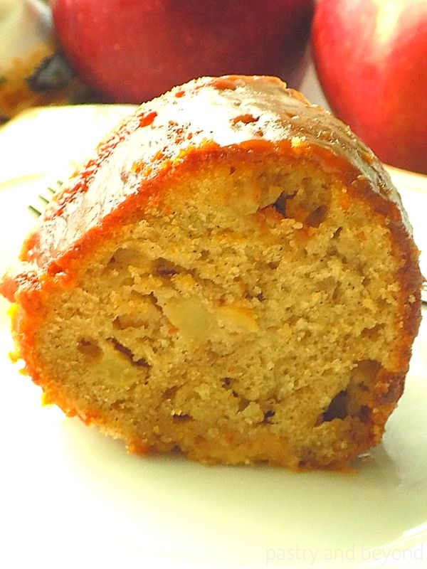 A slice of apple bundt cake on a white plate, apples on the background.