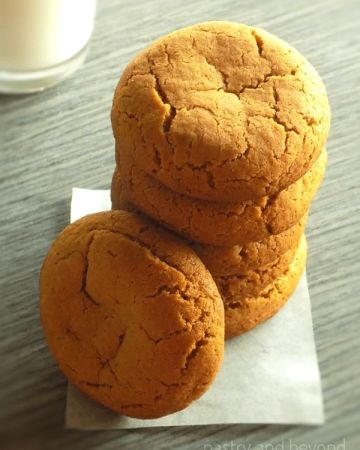 Stacked Ginger Molasses Cookies over parchment paper on a blue-gray surface, milk in a glass on the behind left.