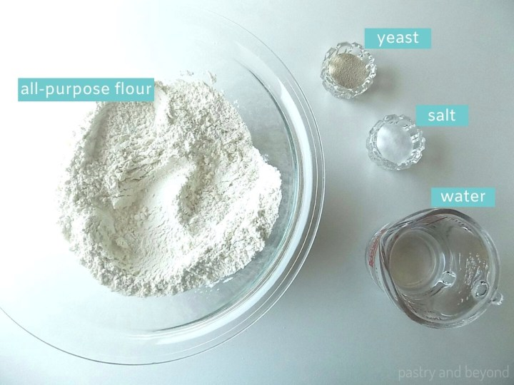 White Bread Ingredients; flour, salt, instant yeast and water on white surface.