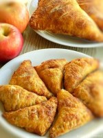 Seven small apple turnovers on a white plate, 2 apples on the back left side. 2 large apple turnovers on a white plate behind the small ones.