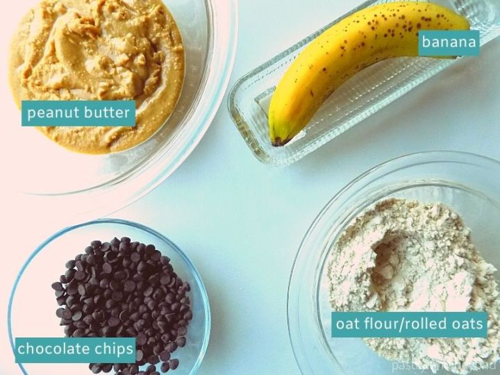 Ingredients for peanut butter banana oat balls on a white surface.