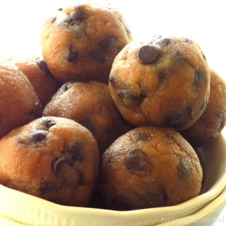 Peanut butter banana balls with chocolate chips randomly stacked in a white bowl.