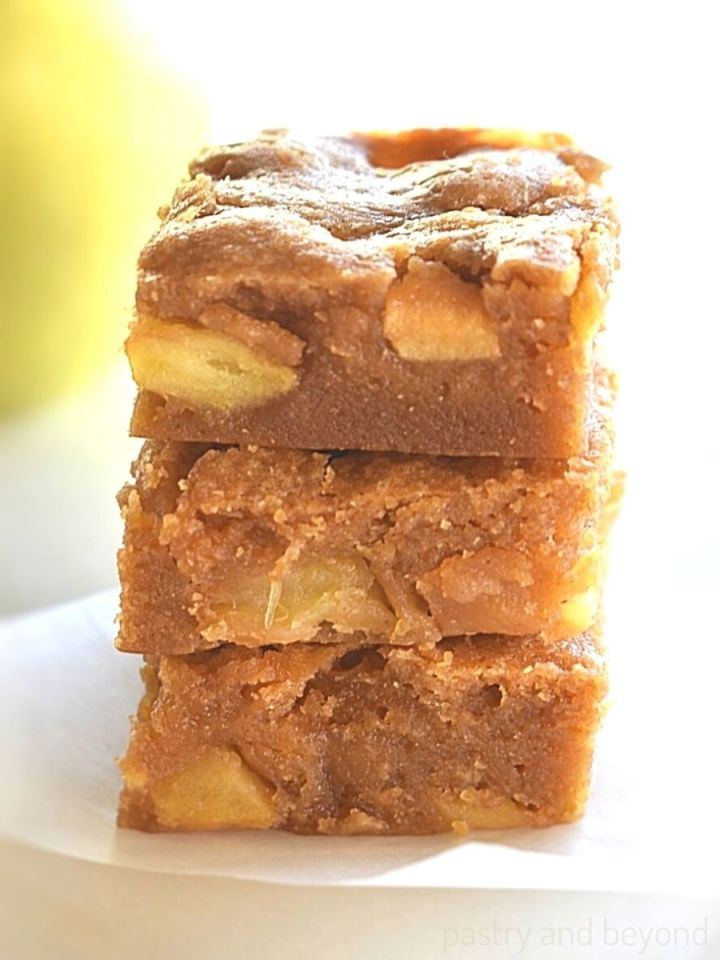 Stacked apple blondies on a parchment paper.