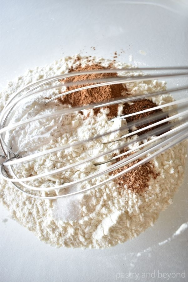 Flour, baking powder, cinnamon, cloves, nutmeg and salt in a bowl with a whisk.