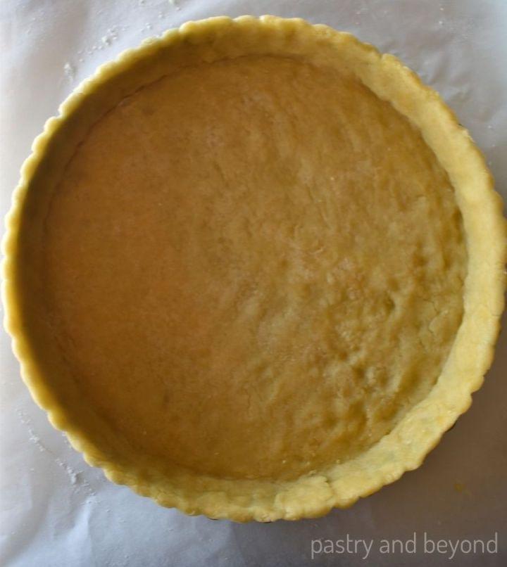 Unbaked tart dough in a tart pan.