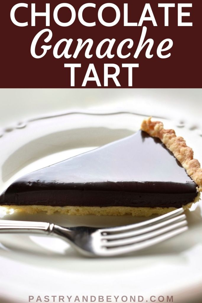 Slice of chocolate ganache tart on a plate with a fork.