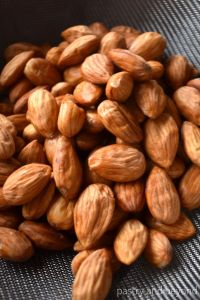 Almonds in a stainer with a shrivel skin.