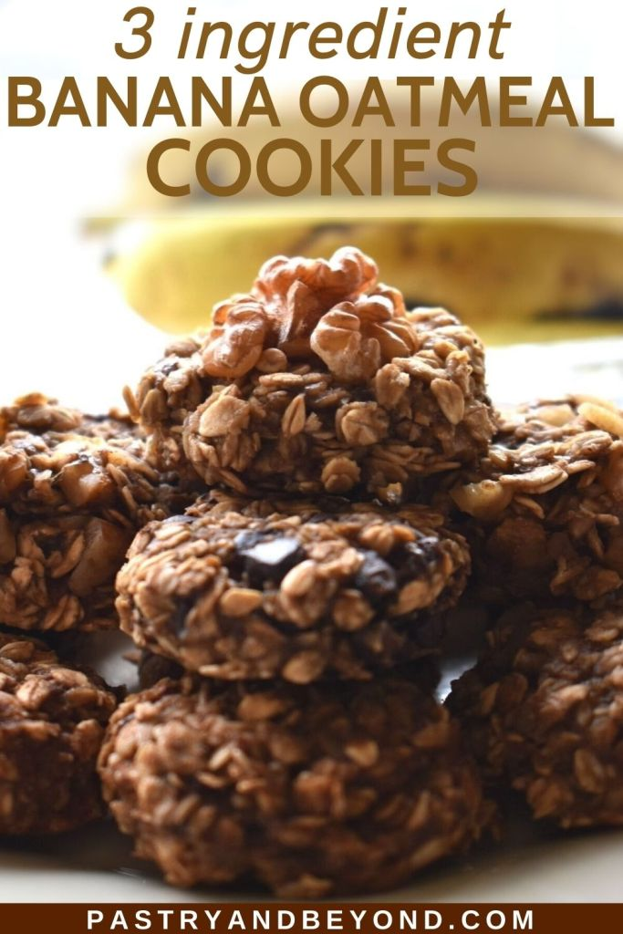 Stacked banana oatmeal cookies on a white plate with bananas in the background.