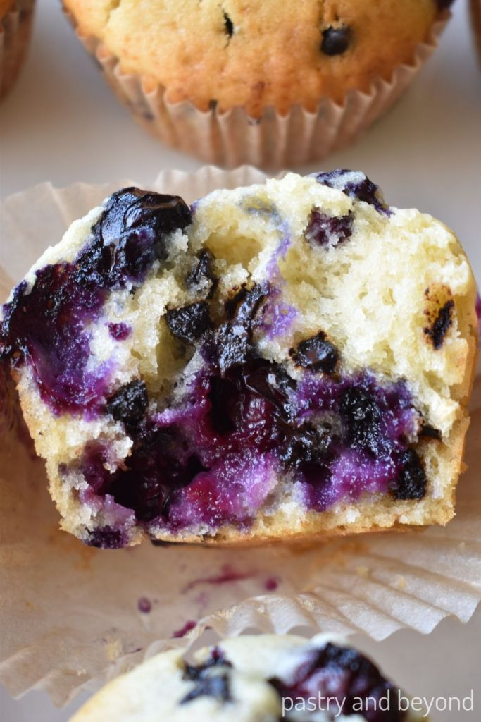 Half of the blueberry muffin with chocolate chips on a muffin liner.