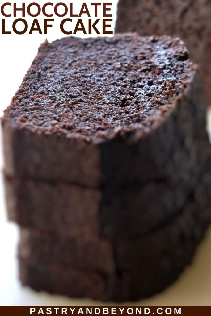 Stacked chocolate loaf cake slices on a white surface.
