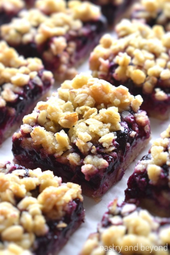 Blueberry oatmeal bars in a row on a parchment paper.