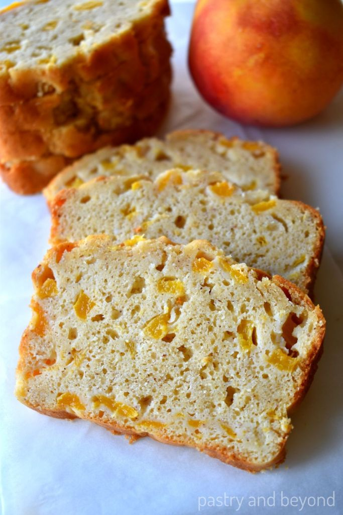 Slices of peach bread with stacked slices and peach in the background.