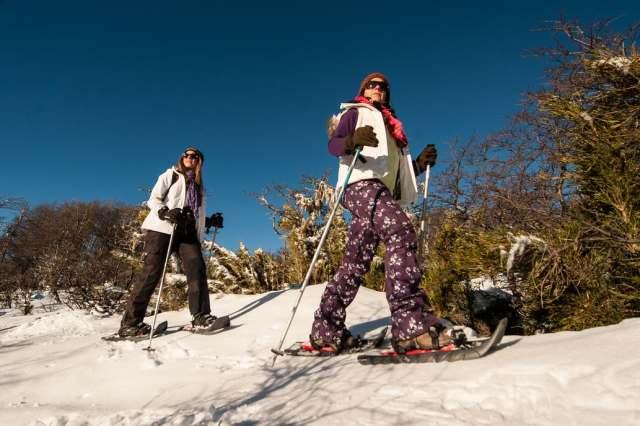 Turistas caminando con raquetas en la nieve en Parque Lanín