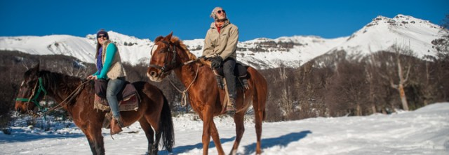 pareja a caballo en la nieve