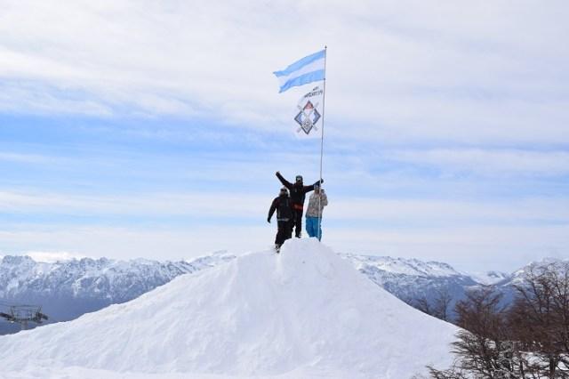 Tres personas sosteniendo el mástil donde flamean las banderas de Argentina y del Club Andino Piltriquitrón