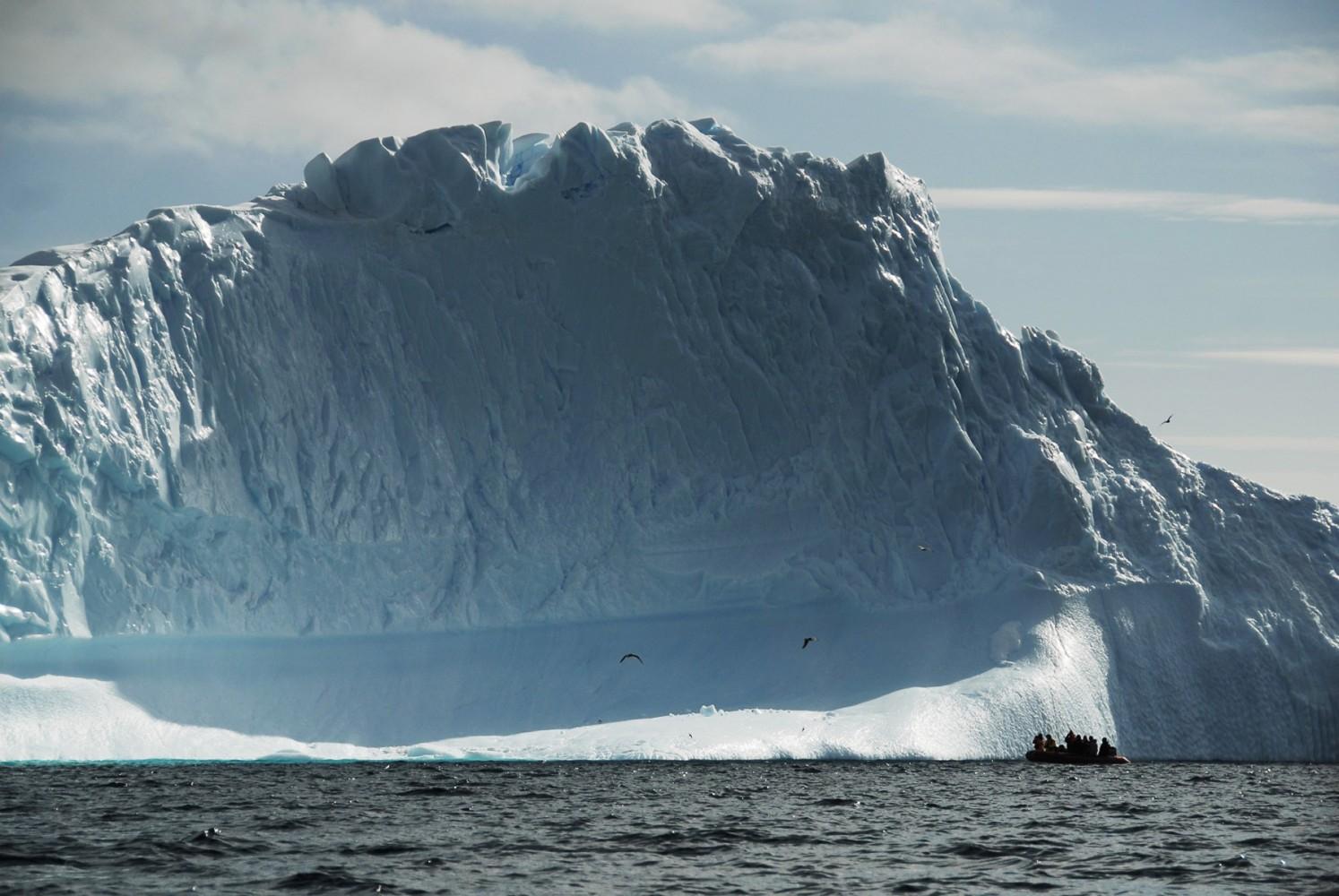 Lateral de un glaciar, con un bote de navegación debajo.