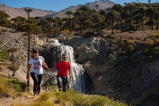 Pareja agarrada de la mano con una cascada de fondo y bosques de araucarias. Parte del recorrido del sendero de las cascadas de Caviahue.