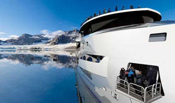 Lateral del crucero que va a la Antártida con montañas nevadas de fondo.