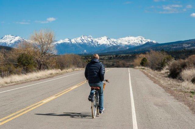 Hombre andando en bicicleta con la montaña de fondo en Esquel.