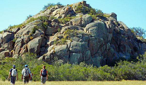 Personas realizando el sendero de frente a una gran roca en el parque Patagonia.