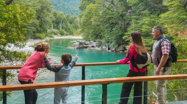 Familia mirando el lago, en el Parque Nacional Los Alerces, compartido por Trevelin y Esquel. Una de las grandes propuestas para el verano