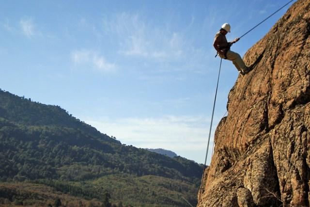 Hombre escalando un risco en Villa Pehuenia. Otras de las 7 razones para visitar la localidad.