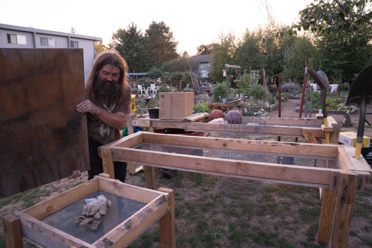 He shows off his system for straining the rocks out of the dirt for his gardening.