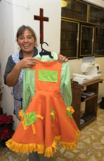 María Elena Neri in her home sewing studio. The orange dress is a costume, but mostly she sews school uniforms.
