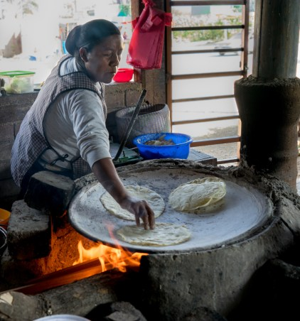Margarita Gomez makes tortillas over a wood-fired clay oven. Her fingers are smooth and delicate but she can flip the hot tortillas somehow.