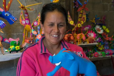 Gloria Ines Gomez Santiago with a partially painted alebrije in her workshop.
