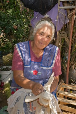 Jesús Jimenez Hernandez makes alebrijes in her home workshop in Arrazola, south of Oaxaca. She sands each carved figure, like the fish in her hands, for about two hours before painting. She's proud that the figures are made from a single piece of wood.