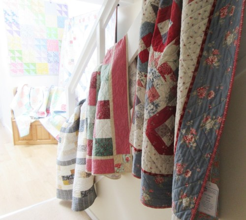 Quilts on the banisters by Allison Reid